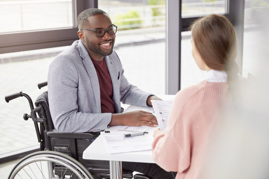 Portrait of male invalid who can`t go, sits in wheelchair, being paralyzed, still work in his own company as director, gives commands and instruction to female secretary, happy to receive high profit